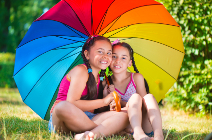 Happy sisters under colorful umbrella in park